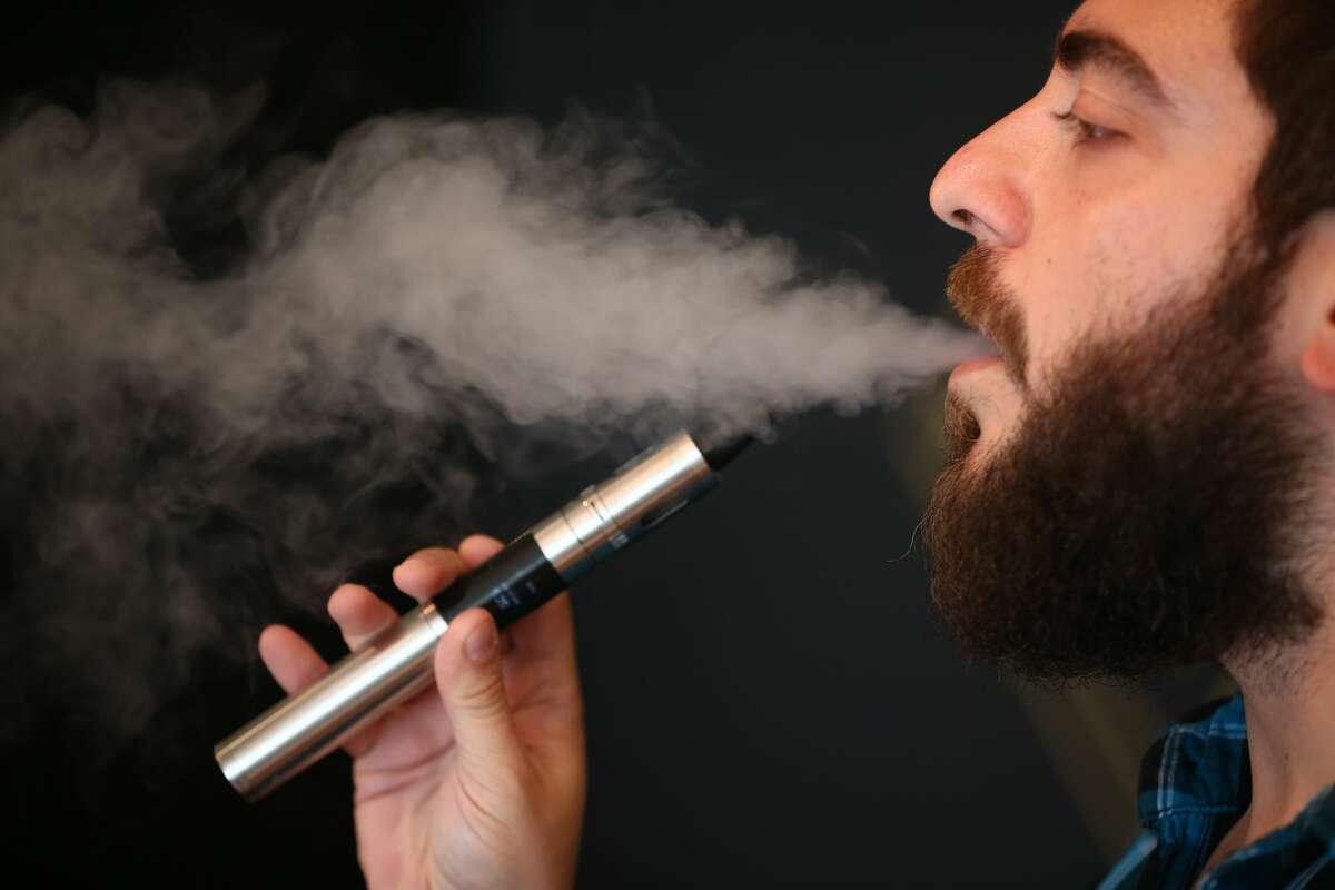 Vape Lab employee Leonardo Verzaro uses an E-Cigarette while working on August 27, 2014, in London, England.