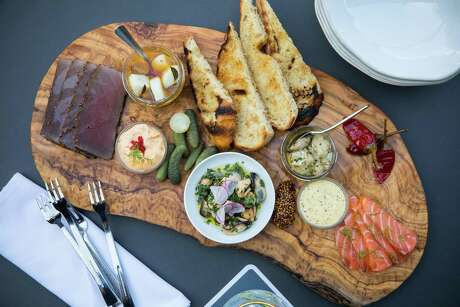the 1751 Charcuterie Board includes house-made cured and smoked seafood such as salmon gravlax, cured tuna, smoked oysters, anchovies, scallop conserva, mustards and pickles.