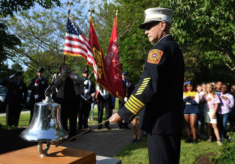 Milford Fire Chief Doug Edo rings a bell three times for the three Milford residents killed in the September 11 attacks on the World Trade Center during the annual Milford Remembers ceremony at the Live Oaks School Memorial Garden in Milford, Conn. on Wednesday, September 11, 2019. Photo: Brian Pounds / Hearst Connecticut Media / Connecticut Post