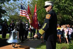 Milford Fire Chief Doug Edo rings a bell three times for the three Milford residents killed in the September 11 attacks on the World Trade Center during the annual Milford Remembers ceremony at the Live Oaks School Memorial Garden in Milford, Conn. on Wednesday, September 11, 2019.
