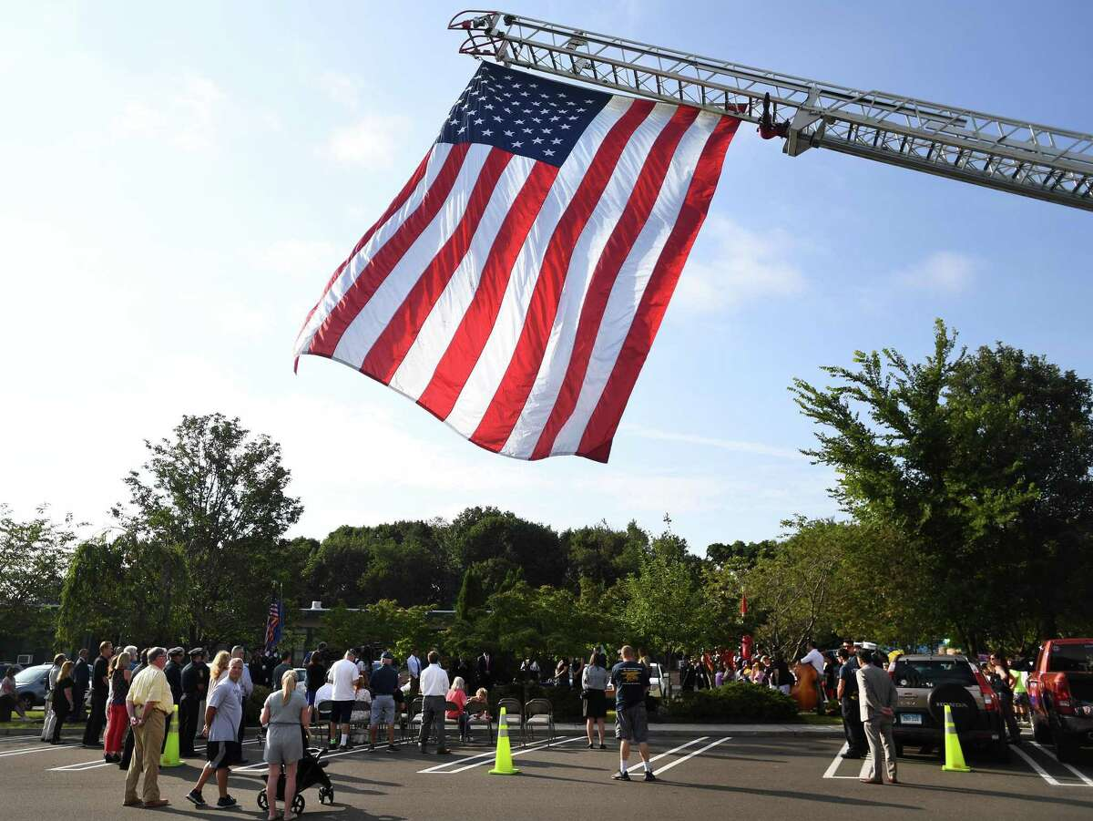A giant American flag hangs from the extended ladder or a fire truck over the annual Milford Remembers 9/11 ceremony at the Live Oaks School Memorial Garden in Milford, Conn. on Wednesday, September 11, 2019.