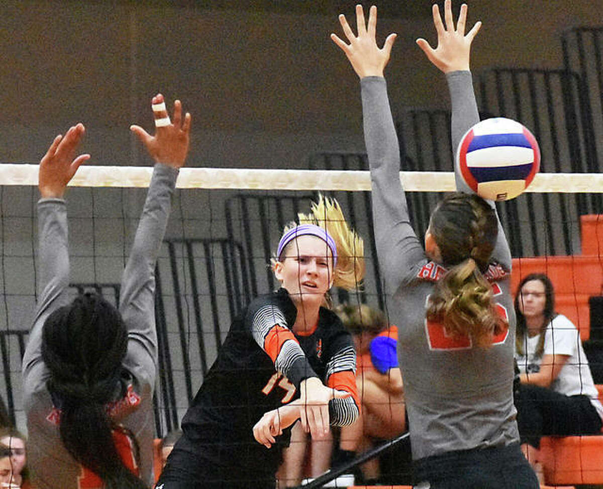Edwardsville's Maddie Isringhausen (middle) gets a kill through the block put up by Alton's Brooke Wolff (right) and Renee Raglin on Tuesday night at Lucco-Jackson Gym in Edwardsville.