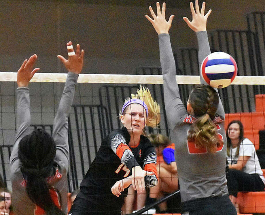 Edwardsville's Maddie Isringhausen (middle) gets a kill through the block put up by Alton's Brooke Wolff (right) and Renee Raglin on Tuesday night at Lucco-Jackson Gym in Edwardsville. Photo: Matt Kamp / Hearst Illinois