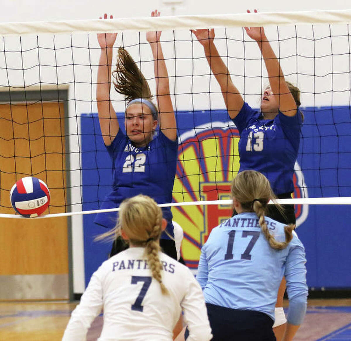 Marquette Catholic's Natalie Ellebracht (22) and Kristine Lauritzen (13) score off a block against Jersey last month at the Roxana Tourney. Ellebracht had six kills and two blocks for the Explorers' in a three-set victory over Hillsboro in Alton.
