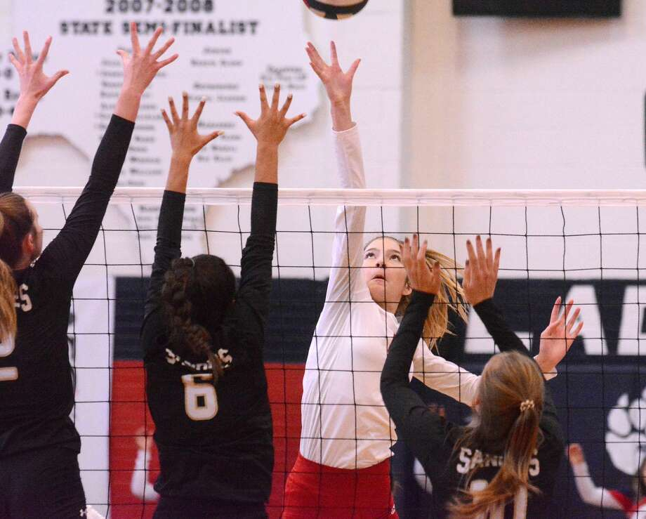 Plainview's Adri Martin skies for the ball at the net against the defense of Amarillo players Currie Marusak (left), Symone Quiles (6) and Kenley Weeks during their District 3-5A volleyball match on Tuesday night in the Dog House. Amarillo won 3-0. Photo: Nathan Giese/Planview Herald