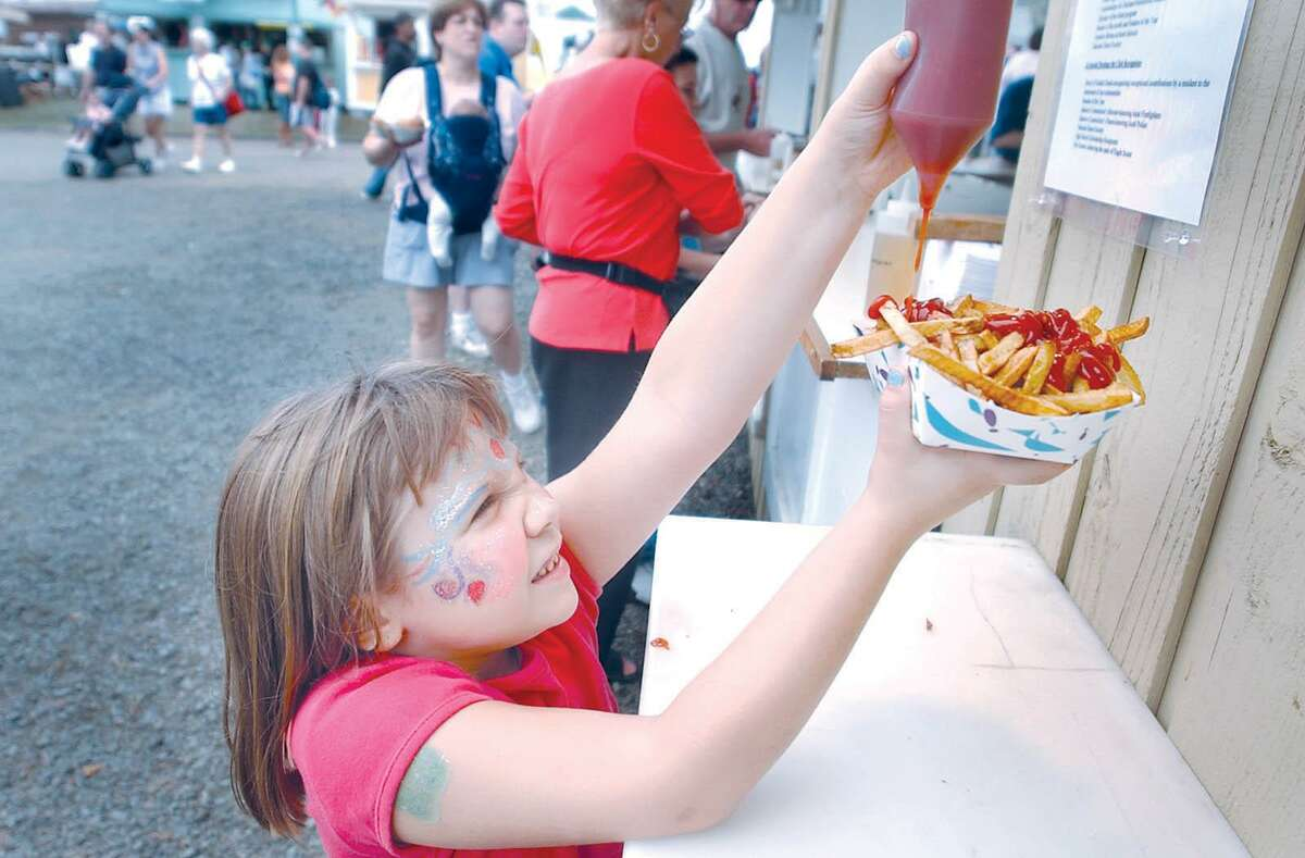Samantha Seco reaches up for a squirt of ketchup on her french fries during the Durham Fair in this archive photograph.