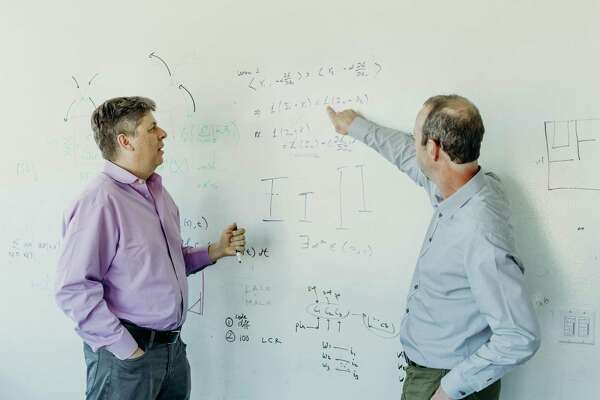 Oren Etzioni, left, who oversees the Allen Institute for Artificial Intelligence, speaks with Peter Clark, manager of the Aristo project, at the lab in Seattle, Aug. 27, 2019. On Wednesday, Sept. 4, the Allen Institute unveiled Aristo, a new system that correctly answered more than 90 percent of the questions on an eighth-grade science test and more than 80 percent on a 12th-grade exam. (Kyle Johnson/The New York Times)
