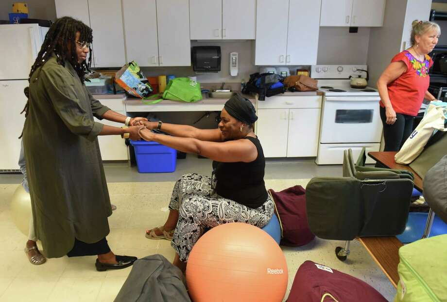 Doula trainer Chanel Porchia-Albert, founder and CEO of Ancient Song Doula Services, left, lifts BirthNet board member Esther Patterson, center, from her seat, a technique taught to prospective doulas, on Friday, Sept. 6, 2019, as the group prepared for a doula training session at the Baby Institute in Albany, N.Y. The Capital Region nonprofit is organizing doula training for local women of color. Doulas are professionals who support women through pregnancy, birth and postpartum by educating and advocating for them. (Will Waldron/Times Union) Photo: Will Waldron, Albany Times Union / 40047774A