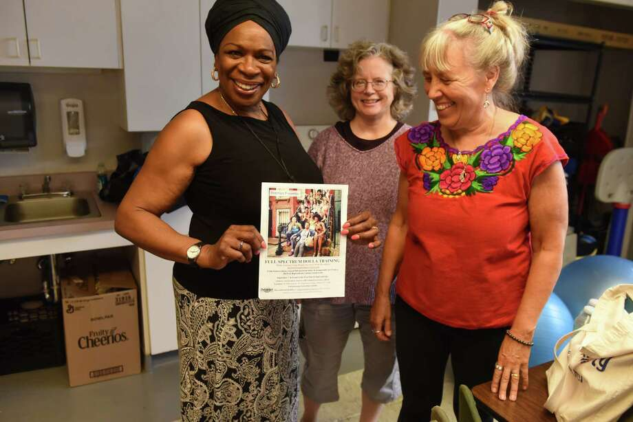 BirthNet board members; Esther Patterson, left, Caroline Keith, center, and Betsy Mercogliano, right, hold a poster for an upcoming doula training workshop on Friday, Sept. 6, 2019, at the Baby Institute in Albany, N.Y. The Capital Region nonprofit is organizing doula training for local women of color. Doulas are professionals who support women through pregnancy, birth and postpartum by educating and advocating for them. (Will Waldron/Times Union) Photo: Will Waldron, Albany Times Union / 40047774A