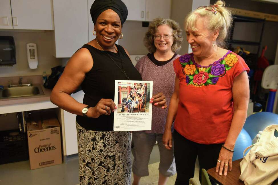 BirthNet board members; Esther Patterson, left, Caroline Keith, center, and Betsy Mercogliano, right, hold a poster for an upcoming doula training workshop on Friday, Sept. 6, 2019, at the Baby Institute in Albany, N.Y. The Capital Region nonprofit is organizing doula training for local women of color. Doulas are professionals who support women through pregnancy, birth and postpartum by educating and advocating for them. (Will Waldron/Times Union)