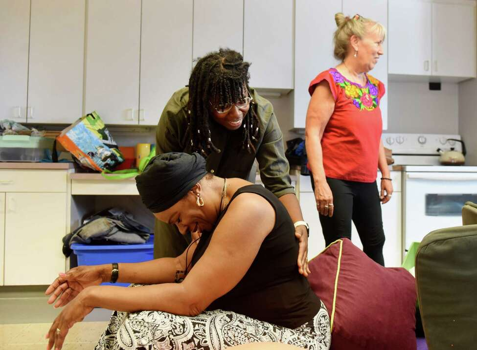 Doula trainer Chanel Porchia-Albert, founder and CEO of Ancient Song Doula Services, top, rubs the back of BirthNet board member Esther Patterson, a technique taught to prospective doulas, on Friday, Sept. 6, 2019, as the group prepared for a doula training session at the Baby Institute in Albany, N.Y. The Capital Region nonprofit is organizing doula training for local women of color. Doulas are professionals who support women through pregnancy, birth and postpartum by educating and advocating for them. (Will Waldron/Times Union)