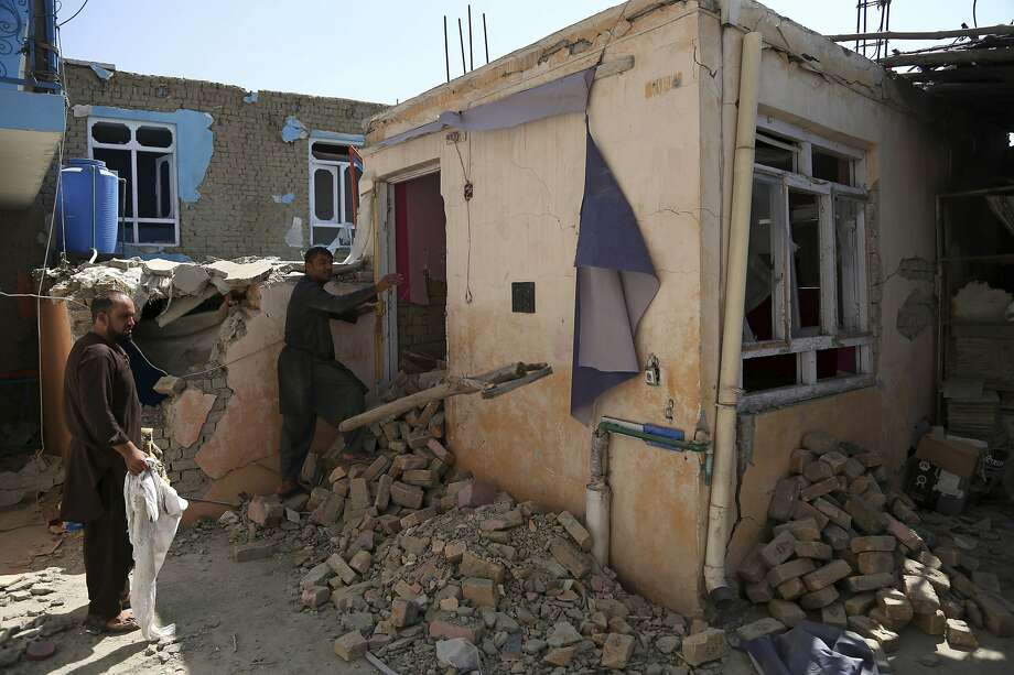 Afghans inspect their home after the bombing of a nearby compound housing foreigners in Kabul. Photo: Rahmat Gul / Associated Press