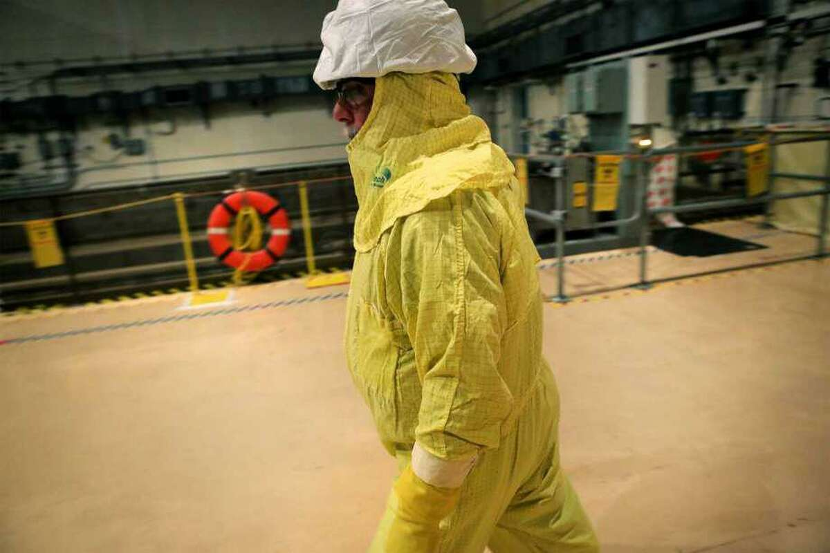 A worker clad in protective ware walks past the spent fuel pool at the South Texas Nuclear Project Electric Generating Station. Bob Owen /San Antonio Express-News