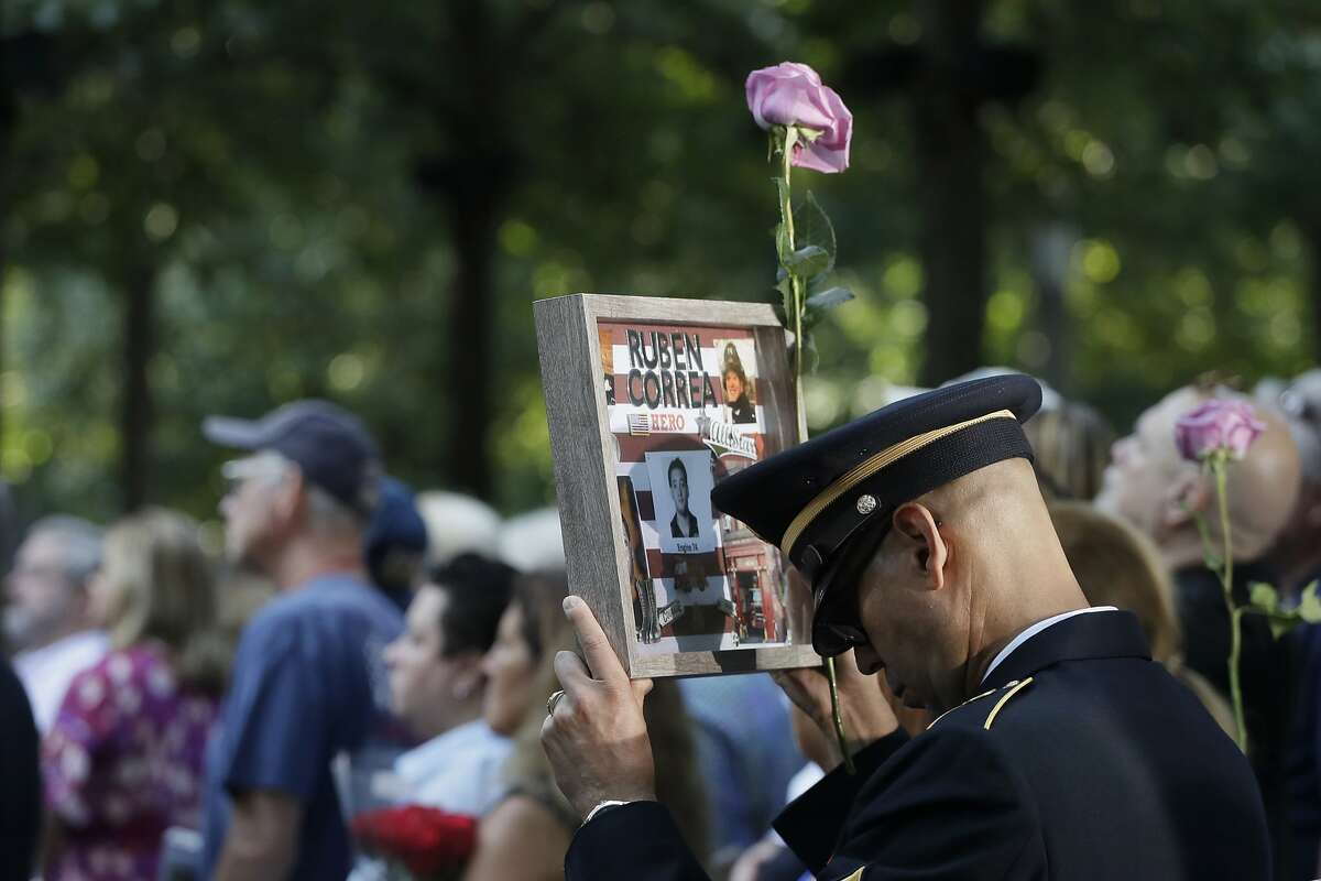 A man holds a photo of a victim during a ceremony marking the 18th anniversary of Sept. 11, 2001 attacks in New York.