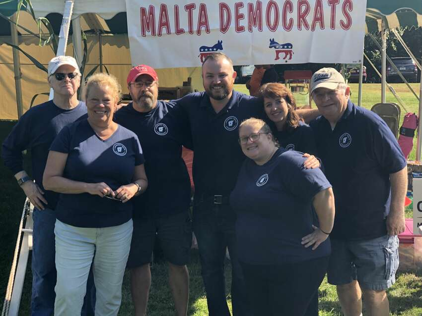 Malta Democrats pose in front of their booth at Community Day in Malta where members sell hamburgers and hotdogs.