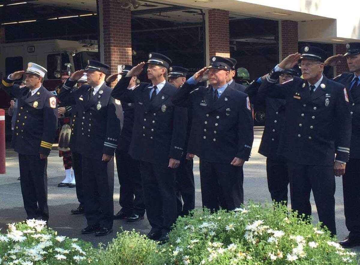 Wilton firefighters salute the flag during the 9/11 remembrance services on Sept. 11, 2019.