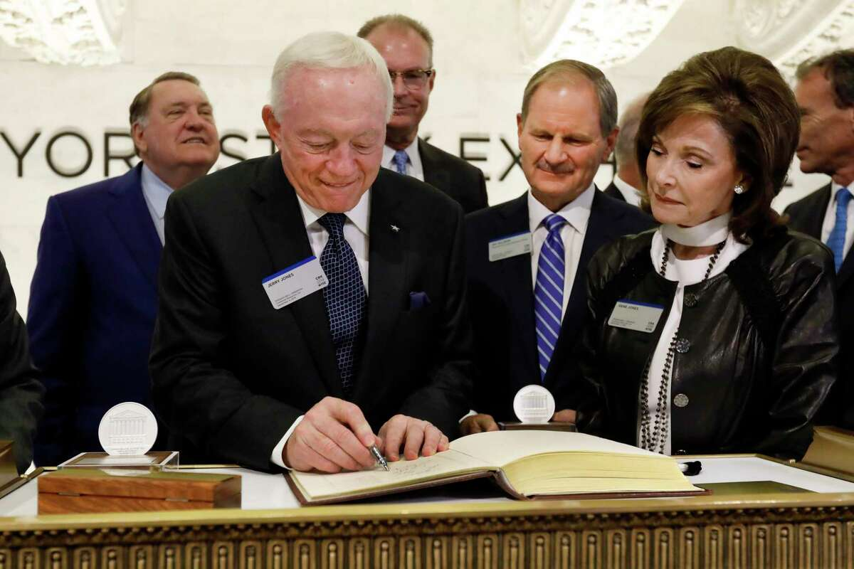 Dallas Cowboys owner, and major stockholder of Comstock Resources Jerry Jones, with wife Gene, signs the guest book before ringing the New York Stock Exchange opening bell, Wednesday, Sept. 4, 2019. The company is celebrating its $2.2 billion acquisition of Covey Park Energy. At center is Chairman & CEO of Comstock Resources Jay Allison. (AP Photo/Richard Drew)