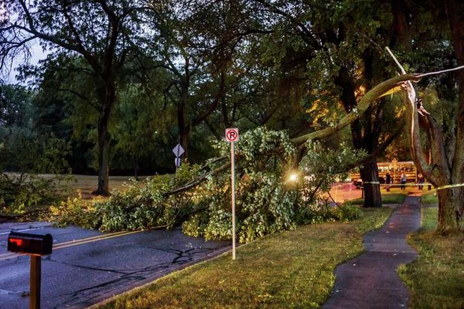 Swede Avenue is blocked off by caution tape near Haley Street after a tree fell and blocked the road during a thunderstorm Tuesday evening in Midland. For more photos of storm damage, go to www.ourmidland.com. (Katy Kildee/kkildee@mdn.net)