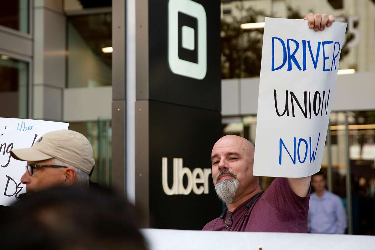 """Gary Branson, a driver with both Uber and Lyft, holds up a sign reading """"Driver Union Now"""" during a protest outside of Uber's Headquarters on Market Street in San Francisco, Calif. on Tuesday, August 27, 2019. Tuesday's protest is part of a three-day drive from Los Angeles to Sacramento to advocate for bill AB5 that would classify gig workers as employees."""