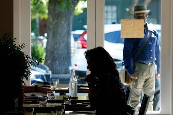 Katherine McLain sits down for lunch while a man outside reads the menu posted on the window at the newly reopened South Park Cafe in San Francisco, Calif. on Wednesday, Sept. 11, 2019. Tech startup Brex purchased and renovated the cafe after it had been closed for over a year.