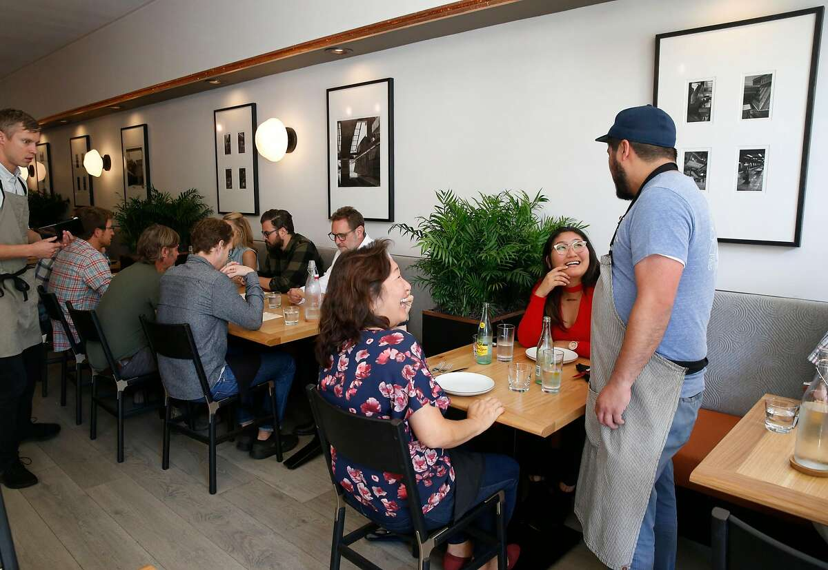 Head chef Peter Mosqueda (right) greets guests Katherine McLain (left) and her daughter Madeline Hahn, who is celebrating her birthday, at the newly reopened South Park Cafe in San Francisco, Calif. on Wednesday, Sept. 11, 2019. Tech startup Brex purchased and renovated the cafe after it had been closed for over a year.