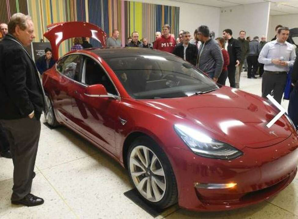 People check out the Model 3 Tesla during TeslaOs Model 3 Road Trip and Policy Forum at the Empire State Plaza Concourse on Monday, Feb. 26, 2018 in Albany, N.Y.