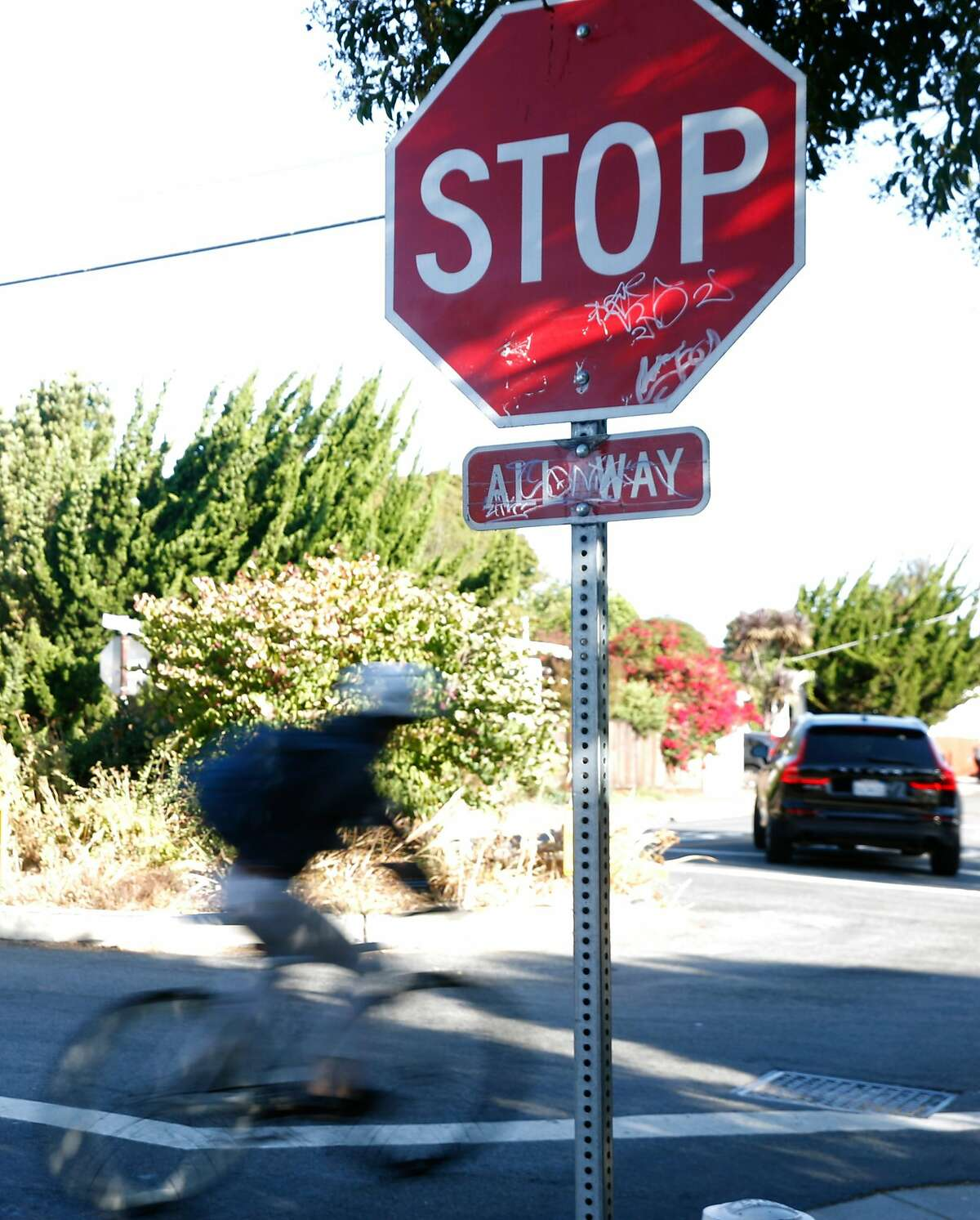 A blcyclist rolls through a stop sign at Bancroft Way and California Street in Berkeley, Calif. on Wednesday, Sept. 11, 2019. Berkeley Police are issuing $300 citations to bicyclists who blow through stop signs or red lights.