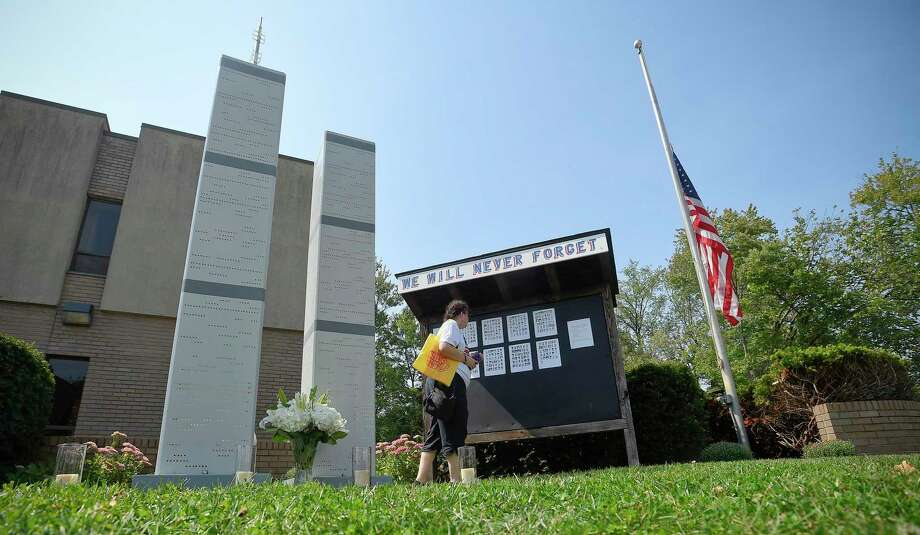 Christine Shaw of Stamford takes a moment to visit a 9/11 memorial on Sept. 11, 2019 set up in front of the Woodside #5 Stamford Fire house that honors the local victims who lost their lives. Shaw, who lost a childhood friend on Sept. 11th, has visited the memorial for the past 18 years. Photo: Matthew Brown / Hearst Connecticut Media / Stamford Advocate