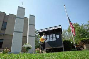 Christine Shaw of Stamford takes a moment to visit a 9/11 memorial on Sept. 11, 2019 set up in front of the Woodside #5 Stamford Fire house that honors the local victims who lost their lives. Shaw, who lost a childhood friend on Sept. 11th, has visited the memorial for the past 18 years.