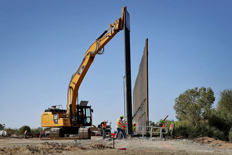 Government contractors erect a section of Pentagon-funded border wall along the Colorado River, Tuesday, Sept. 10, 2019 in Yuma, Ariz. The 30-foot high wall replaces a five-mile section of Normandy barrier and post-n-beam fencing, shown at left, along the the International border that separates Mexico and the United States. Construction began as federal officials revealed a list of Defense Department projects to be cut to pay for President Donald Trump's wall. (AP Photo/Matt York) Photo: Matt York, Associated Press