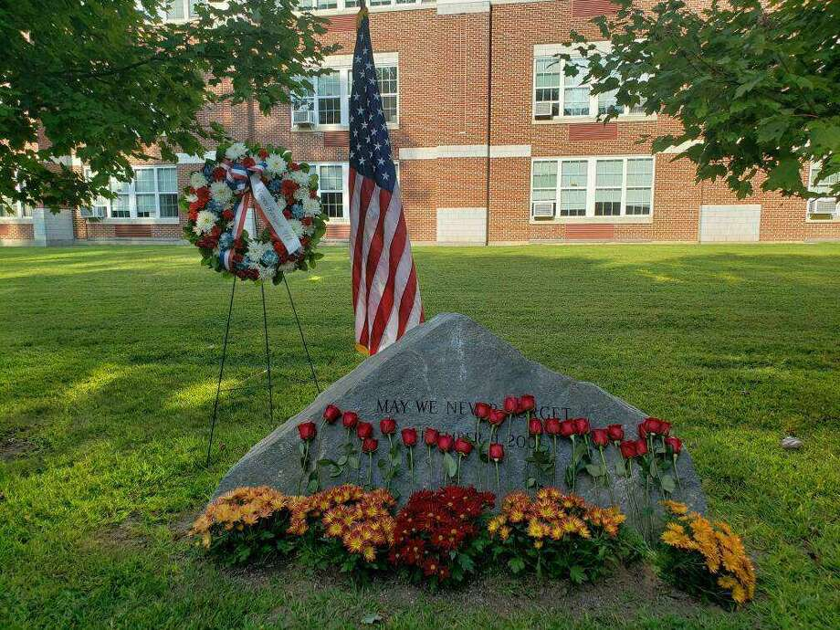 Attendees placed roses on Darien's 9/11 memorial, located behind Middlesex Middle School, during the ceremony. Photo: Sandra Diamond Fox /Hearst Connecticut Media /