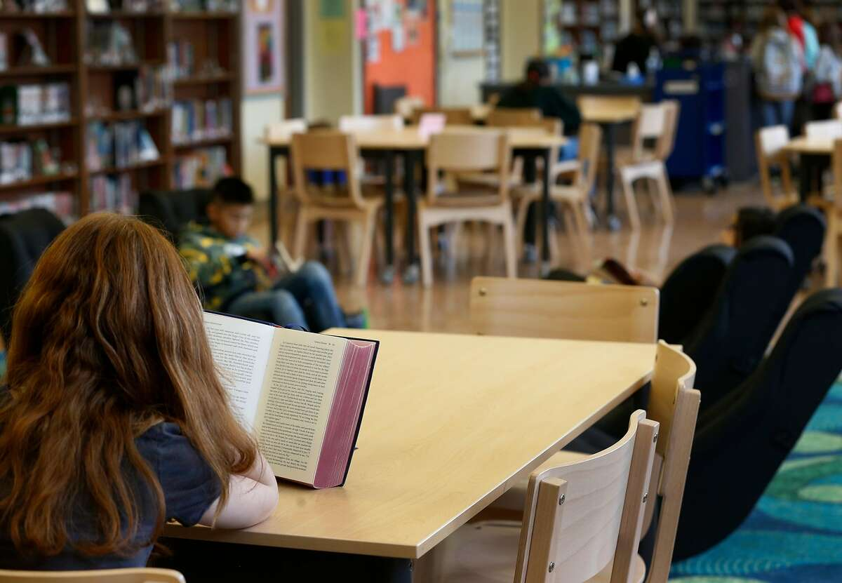 Students read books in the Presidio Middle School library in San Francisco, Calif. on Tuesday, Sept. 10, 2019. Salesforce provided funds to refurbish and upgrade the schoolyard and library.
