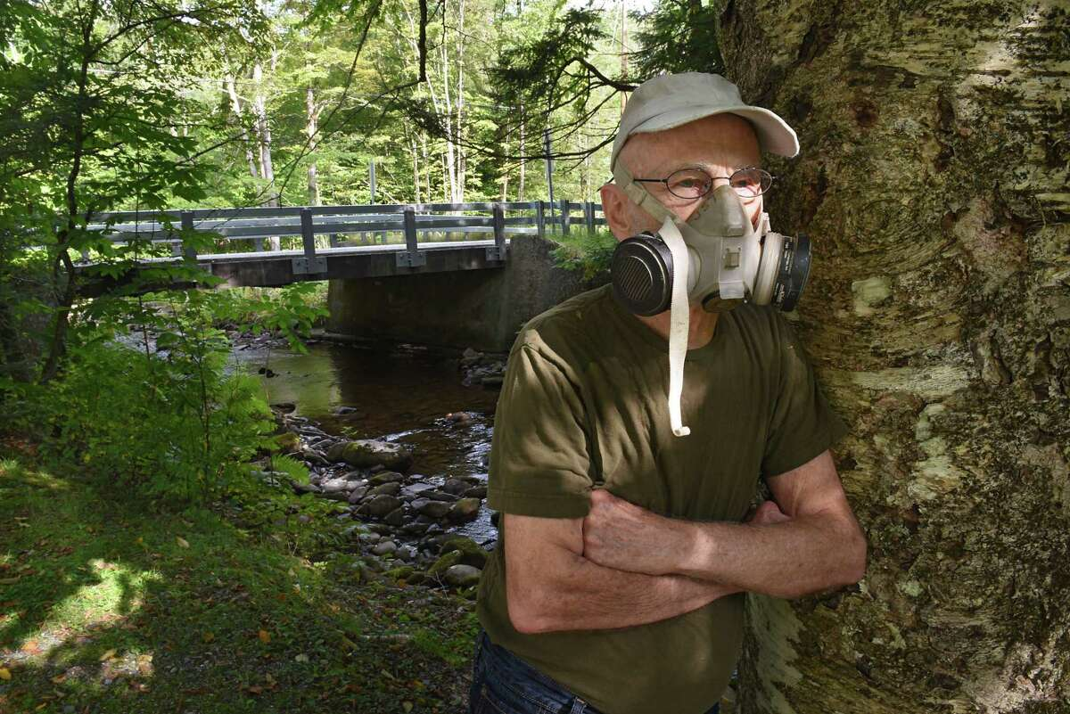 Jack Spillman stands with the creosote wooden bridge installed in front of his house by the county in the background on Wednesday, Sept. 11, 2019 in Stephentown Center, N.Y. He's been having respiratory problems all summer since it was put in. (Lori Van Buren/Times Union)