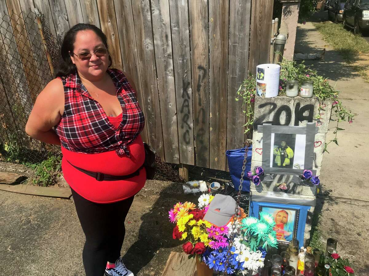 Emily Soto, 28, of Stamford standing next to the memorial to Leobardo Quintero, who died after being pushed to the ground on lower Alden Street last week.