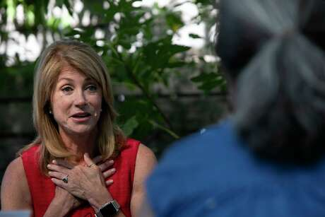 """Wendy Davis visits with a group of community members, including Trish Florence, right, a mother of two autistic sons who is concerned about the link between health care and education, during Davis' """"listening tour"""" at CommonWealth Coffeehouse & Bakery in San Antonio on Friday, July 26, 2019."""