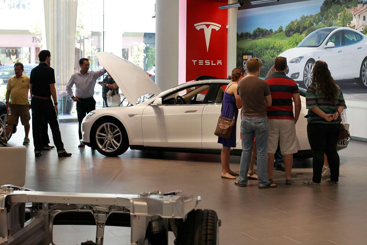 Visitors tour the all electric vehicles at the Tesla showroom in the Santana Row shopping center in San Jose, Calif. on Tuesday July 30, 2013. Tesla sells directly to customers, rather than working through franchise auto dealers. Existing dealers consider that a threat. So in state after state (except California), the dealers have tried to shut out Tesla by asking legislators to tweak existing laws that protect franchises. Tesla runs a network of