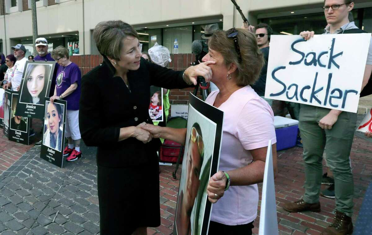 In this Aug. 2, 2019, file photo, Massachusetts Attorney General Maura Healey, left, wipes a tear from the face of Wendy Werbiskis, of East Hampton, Mass., one of the protesters gathered outside a courthouse in Boston, where a judge was to hear arguments in the state's lawsuit against Purdue Pharma over its role in the national drug epidemic.