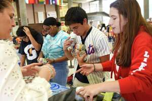 Students collect food during the ninth annual September 11th National Day of Service and Remembrance food drive at Greenwich High School on Wednesday. With the help of the GHS Roots & Shoots Club and Heroes Club, students and staff pledged to collect at least 2,977 non-perishable food items in memory of each victim of the 9/11 attacks 18 years ago. Donations piled up throughout the day in the middle of the student center and will be provided to the Neighbor-to-Neighbor food pantry.