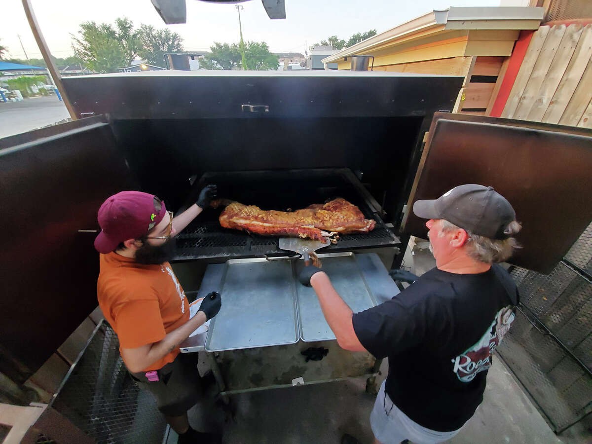 Russell Roegels and pitmaster Alfredo Tapia remove a whole hog from a custom Bewley hog cooker at Roegels Barbecue Co.