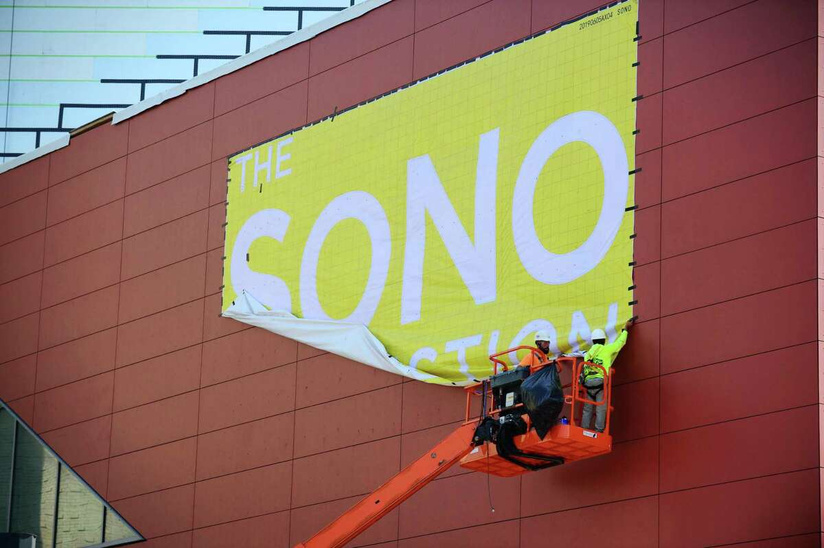 Construction workers with Brookfield Properties remove a banner for the SoNo Collection Mall Wednesday, September 11, 2019, in Norwalk, Conn. The mall is scheduled to open next month.