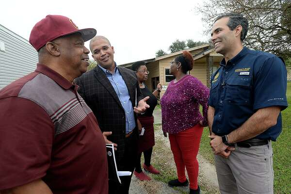 Texas Land Commissioner George P. Bush jokes with Port Arthur councilman Cal Jones and Mayor Derrick Freeman as area GLO employee Rhonda Masters talks with homeowner Havalisia Owens about obtaining assistance during a stop in Jefferson County Wednesday. The Texas General Land Office rolled out their newest Homeowner Assistance Program in the region to further aid those still recovering from Tropical Storm Harvey. They also announced a FEMA extension on trailers as well as a new sales program. Photo taken Wednesday, November 28, 2018 Kim Brent/The Enterprise