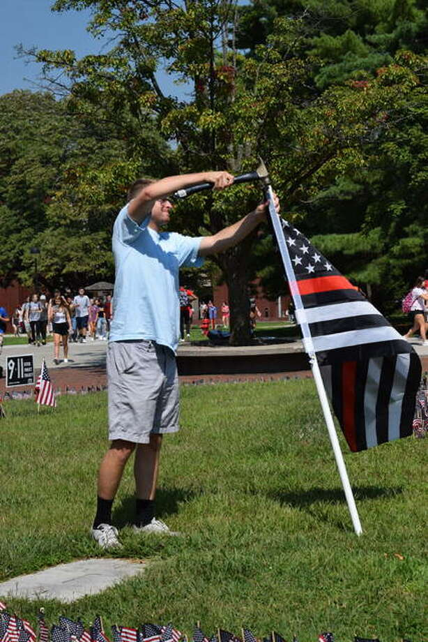 Sigma Phi Epsilon fraternity member Ethan Coderre pounds in a red thin line flag to symbolize firefighters. The flag is one of two first responder flags donated by the fraternity to the College Republicans memorial for 9/11. Photo: Tyler Pletsch | The Intelligencer