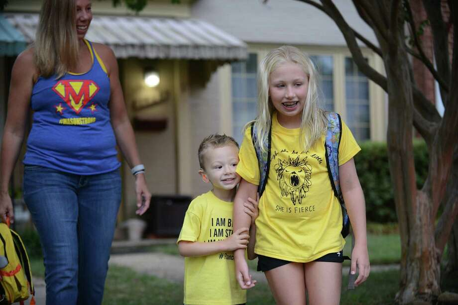 Whitaker Weinburger, his sister Lakeland and his mother, Erin Weinburger, leave their home in Alexandria, Virginia, to see more than 100 yellow cars lined up in the street and neighbors decorating their homes to celebrate Whitaker's fourth birthday on Wednesday, Sept. 11, 2019. Photo: Photo For The Washington Post By Astrid Riecken. / Astrid Riecken