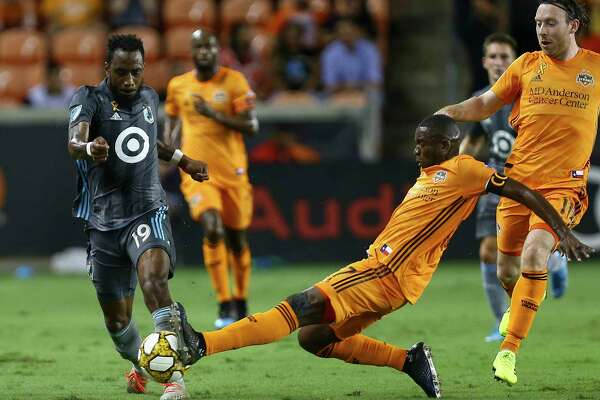 Houston Dynamo midfielder Boniek Garcia (27) pokes the ball away from Minnesota United defender Romain Metanire (19) during the first half of an MLS match at BBVA Stadium Wednesday, Sept. 11, 2019, in Houston.