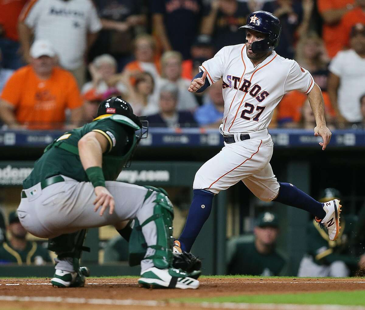 HOUSTON, TEXAS - SEPTEMBER 11: Jose Altuve #27 of the Houston Astros is tagged out by Sean Murphy #12 of the Oakland Athletics in the fifth inning at Minute Maid Park on September 11, 2019 in Houston, Texas. (Photo by Bob Levey/Getty Images)