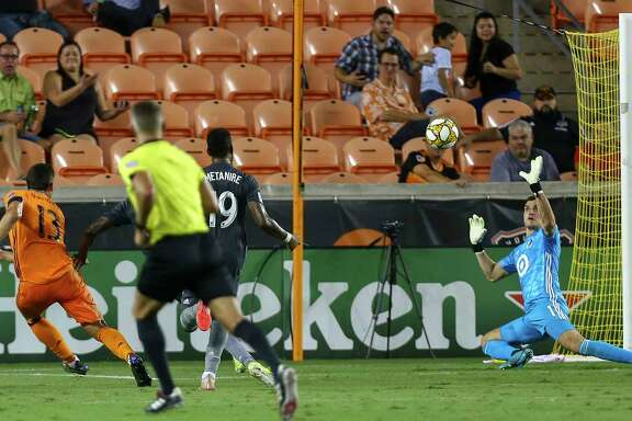 Houston Dynamo forward Christian Ramirez (13) scores a goal against Minnesota United FC goalkeeper Vito Mannone (1) during the first half of an MLS match at BBVA Stadium Wednesday, Sept. 11, 2019, in Houston.