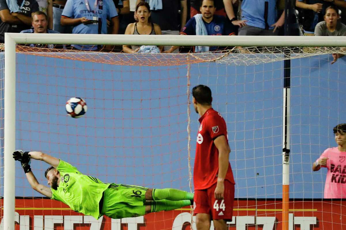 Toronto FC goalkeeper Quentin Westberg (16) deflects a shot on goal by New York City FC's Ronald Matarrita as teammate Omar Gonzalez (44) and fans watch during the second half of an MLS soccer match Wednesday, Sept. 11, 2019, in New York. The game ended in a 1-1 draw. (AP Photo/Frank Franklin II)