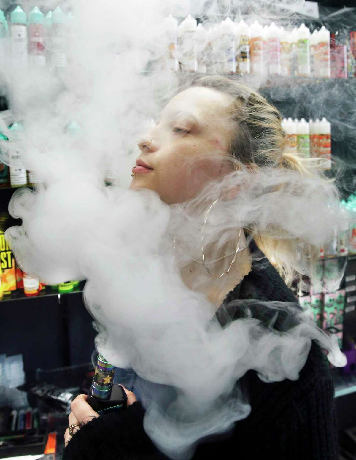 Claire Collingwood is surrounded in a cloud of vapor as she exhales after using a vaping device.
