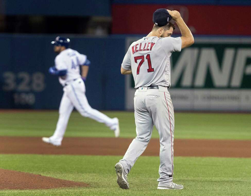 Boston Red Sox relief pitcher Trevor Kelley (71) walks off the mound after giving up a home run to Toronto Blue Jays' Rowdy Tellez rounding the bases behind him during the fourth inning of a baseball game, Wednesday, Sept. 11, 2019 in Toronto. (Fred Thornhill/The Canadian Press via AP)