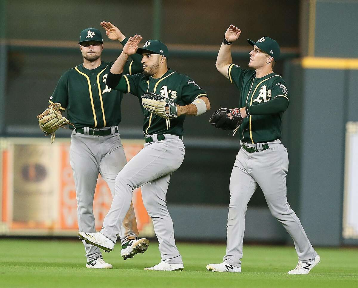 HOUSTON, TEXAS - SEPTEMBER 11: (L-R) Seth Brown #65 of the Oakland Athletics, Ramon Laureano #22 and Mark Canha #20 celebrate after the final out against the Houston Astros at Minute Maid Park on September 11, 2019 in Houston, Texas. (Photo by Bob Levey/Getty Images)